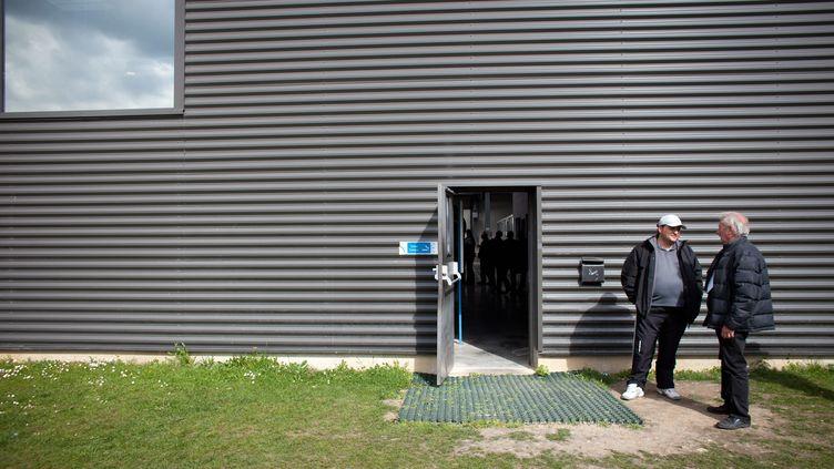 Des ouvriers discutent le 20 avril 2012 à la sortie de l'usine Prevent Glass, en Seine-et-Marne, un sous-traitant de Volkswagen placé en redressement judiciaire depuis novembre 2011. (MARLENE AWAAD / MAXPPP)