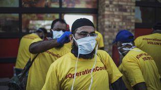 Des bénévoles masqués pour se protéger du coronavirus, dans un township de Johannesburg, le 21 mars 2020. (MARCO LONGARI / AFP)