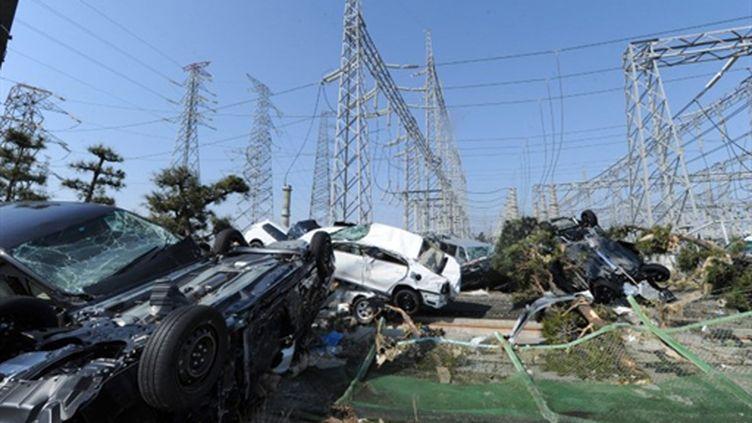 Des voitures jetées par le tsunami aux pieds d'installations électriques, dans la préfecture de Miyagi, le 13 mars 2011. (AFP PHOTO / MIKE CLARKE)