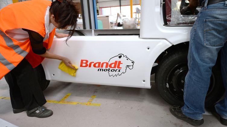Des employés assemblent une voiture électrique ou hybride, le 5 septembre 2012 sur le site Fagor Brandt de Lyon. (PHILIPPE DESMAZES / AFP)