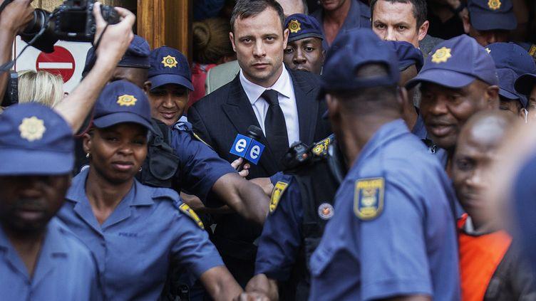 Oscar Pistorius sort du tribunal de Prétoria (Afrique du Sud) encadré par une demi-douzaine de policiers, le 12 septembre 2014 (GIANLUIGI GUERCIA / AFP)