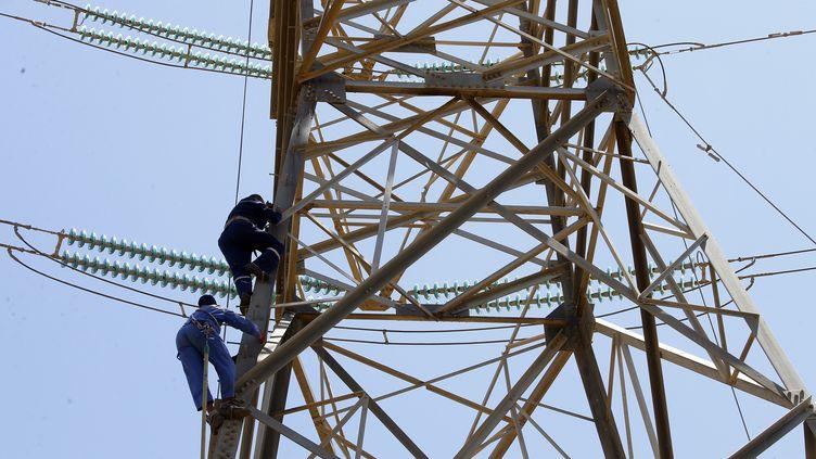 Des techniciens de la Compagnie nationale d'électricité réparent les lignes à haute tension endommagées par les combats au sud de Tripoli, le 23 mai 2019. (MAHMUD TURKIA / AFP)