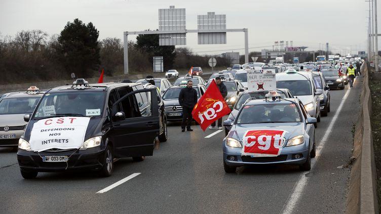 Des taxis bloquent l'autoroute près de l'aéroport de Roissy-Charles de Gaulle (Val-d'Oise), le 10 février 2014. (THOMAS SAMSON / AFP)