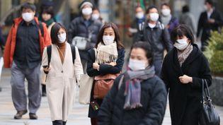 Des passants portent des masques de protection contre le nouveau coronavirus, le 26 février 2020 à Tokyo (Japon). (KAZUKI WAKASUGI / YOMIURI / AFP)