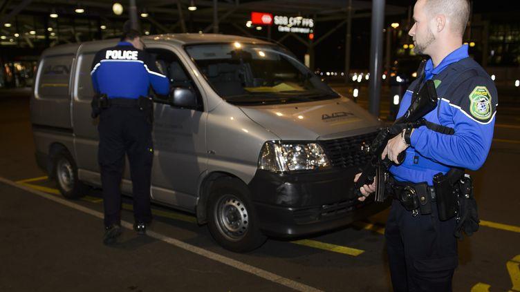 Des policiers contrôlent un véhicule à l'aéroport de Genève, le 10 décembre 2015. (RICHARD JUILLIART / AFP)