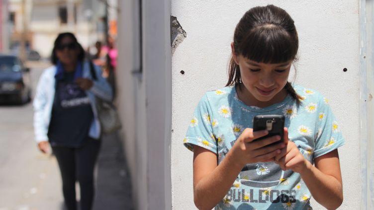 """Une adolescente mexicaine découvre en juillet 2017 l'application """"No estoy sola"""", lancée àCiudadJuárez. (HERIKA MARTINEZ / AFP)"""