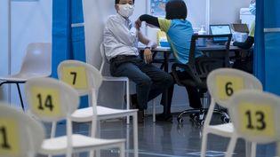 Un homme reçoit une dose du vaccin Sinovac dans un centre de vaccination à Hong Kong (23 février 2021). (PAUL YEUNG / POOL)