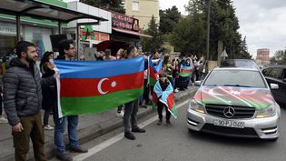 Des personnes tiennent le drapeau de l'Azerbaïdjan afin de célébrer, selon Bakou, la prise de la ville stratégique de Choucha dans le Haut-Karabakh, le 8 novembre 2020 à Bakou (Azerbaïdjan). (TOFIK BABAYEV / AFP)