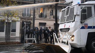 """Un camion de CRS équipé d'un canon à eau tente de disperser les """"gilets jaunes"""" près des Champs-Elysées à Paris, le samedi 1er décembre 2018. (ALAIN JOCARD / AFP)"""