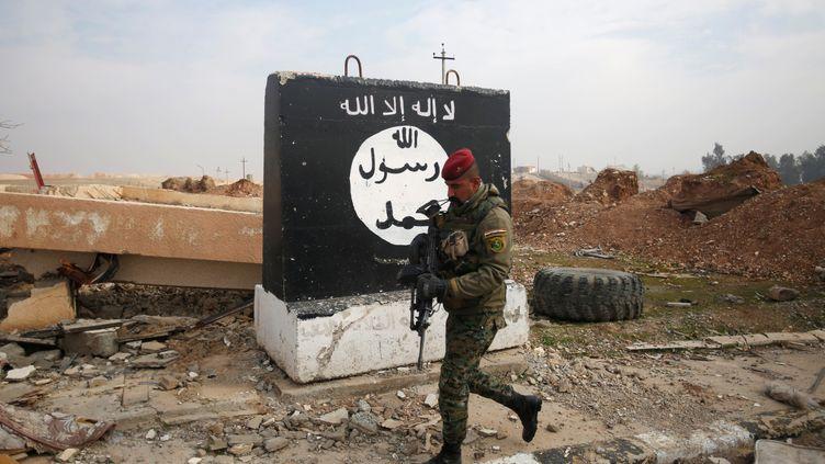 Un soldat irakien devant un drapeau du groupe Etat islamique, le 21 janvier 2017, au nord de Mossoul (Irak). (KHALID AL MOUSILY / REUTERS)