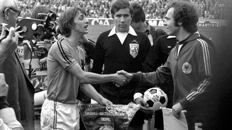 Johan Cruyff, capitaine des Pays-Bas, et Franz Beckenbauer, son homologue ouest-allemand, se saluent avant la finale du Mondial 1974, le 7 juillet 1974 à Munich (Allemagne). (WERNER BAUM / DPA / AFP)