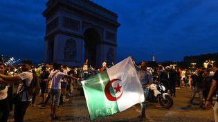 Des supporters algériens près de l'Arc de triomphe sur les Champs-Elysées à Paris, le 11 juillet 2019. (DOMINIQUE FAGET / AFP)