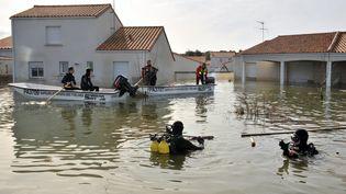 Des plongeurs inspectent des maisons inondées à La Faute-sur-Mer (Vendée), le 2 mars 2010, après le passage de la tempête Xynthia. (FRANK PERRY / AFP)