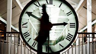 Une personne passe devant une horloge, le 25 mars 2010 au centre commercial de la Toison d'Or, à Dijon. (JEFF PACHOUD / AFP)