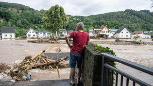 Un homme regarde la maison de ses parents de l'autre côté de la rivière, en Rhénanie-Palatinat (Allemagne), le 15 juillet 2021. (BORIS ROESSLER / DPA / AFP)