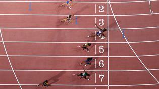 Des athlètes passent la ligne d'arrivée lors de la finale du 100 mètres haies, le 6 octobre 2019, lors des Mondiaux d'athlétisme à Doha (Qatar). (ANTONIN THUILLIER / AFP)