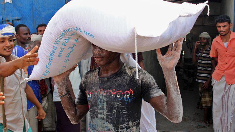 Un travailleur humanitaire transporte un sac de farine donné par le programme alimentaire mondial de l'ONU dans la province d'Hajjah, dans l'ouest du Yémen, le 25 septembre 2018. (ESSA AHMED / AFP)