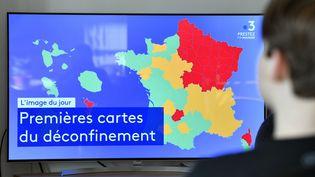 Une femme observe à la télévision, le 30 avril à Nancy (Meurthe-et-Moselle), la carte provisoire des départements classés rouge, orange ou vert enfonction de la circulation du Covid-19. (MAXPPP)