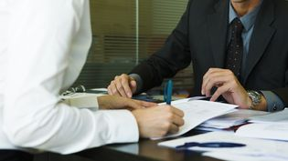 Un jeune diplômé signe un ciontrat d'embauche. (ERIC AUDRAS  / MAXPPP)