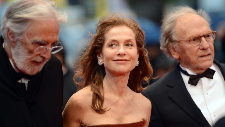"""Le réalisateur autrichien Michael Haneke (à g.) vient présenter """"Amour"""" en présence de deux acteurs du film, Isabelle Huppert et Jean-Louis Trintignant, le 20 mai 2012 à Cannes. (ANNE-CHRISTINE POUJOULAT / AFP)"""