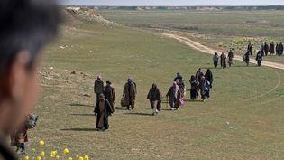 Des hommes soupçonnés d'être des combattants de l'État islamique et leurs familles marchent dans un champ alors qu'ils quittent l'Irak, le 13 février 2019, lors d'une opération des forces démocratiques syriennes dans l'Est de la Syrie. Illustration (FADEL SENNA / AFP)