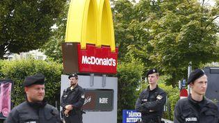 Des policiers montent la garde, samedi 22 juillet, devant le restaurant McDonalds où un jeune homme avait ouvert le feu, la veille, tuant neuf personnes. (ARND WIEGMANN / REUTERS)