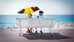 Un couple regarde la mer à Nice (Alpes-Maritimes) en portant des masques sanitaires, le 2 août 2020. (ARIE BOTBOL / HANS LUCAS / AFP)