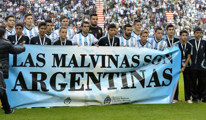 """Les joueurs de l'équipe d'Argentine tiennent une banderole où il est écrit """"Les Malouines sont argentines"""" à l'occasion d'un match amical face à la Slovénie, le 7 juin 2014 à La Plata (Argentine). (ALEJANDRO PAGNI / AFP)"""