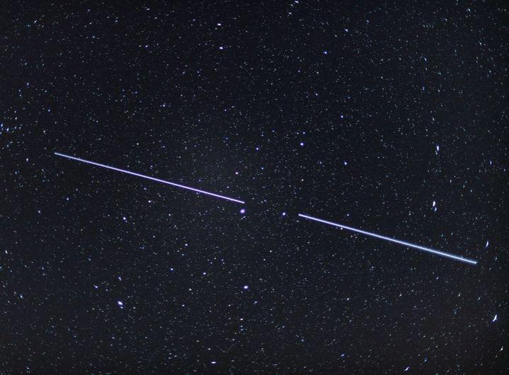 Deux satellites Starlink dans le ciel du Brandebourg (Allemagne) le 18 avril 2020. (PATRICK PLEUL / DPA ZENTRALBILD / DPA PICTURE ALLIANCE / AFP)