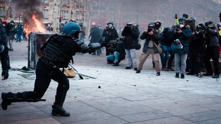 """Place de la République, devant un mur de photographes, un gendarme lance une grenade lacrymogène, lors d'une manifestation de """"gilets jaunes"""" à Paris, le 2 février 2019. (KARINE PIERRE / HANS LUCAS / AFP)"""