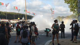 Des policiers emploient des canons à eau contre des manifestants s'opposant au sommet du G7, le 24 août 2019, à Bayonne (Pyrénées-Atlantiques). (GAIZKA IROZ / AFP)