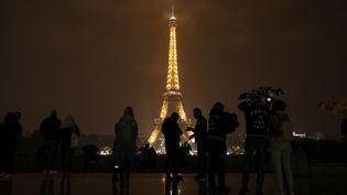 Des personnes devant la tour Eiffel, à Paris, le 2 octobre 2017. (LUDOVIC MARIN / AFP)