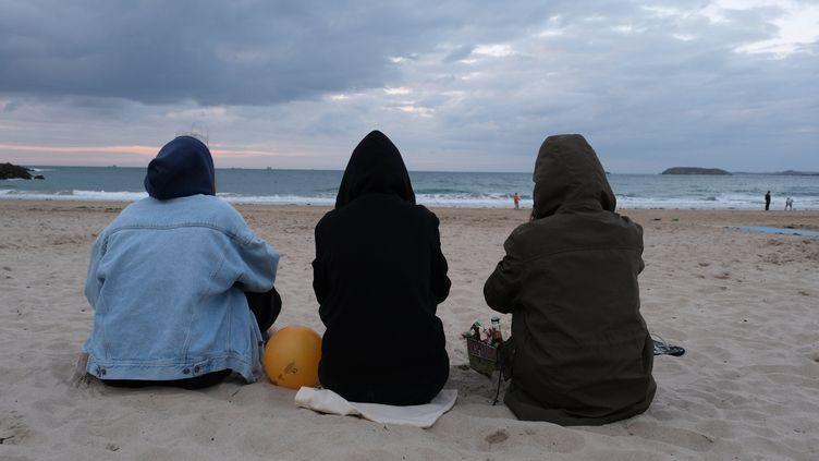 Des vacanciers emmitouflés sur la plage de Dinard (Ille-et-Vilaine), le 28 juillet 2021. (BASTIEN MOIGNOUX / MAXPPP)