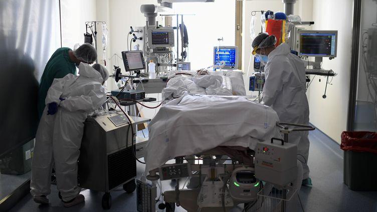 Des soignants auprès d'un patient Covid-19 placé en réanimation, dans un hôpital de Madrid (Espagne), le 15 octobre 2020. (OSCAR DEL POZO / AFP)