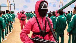 """Les joueurs en vert et les gardes en rouge et masqués dans la série dystopique sud-coréenne """"Squid Game"""" de Netflix. (NETFLIX / YOUNGKYU PARK)"""