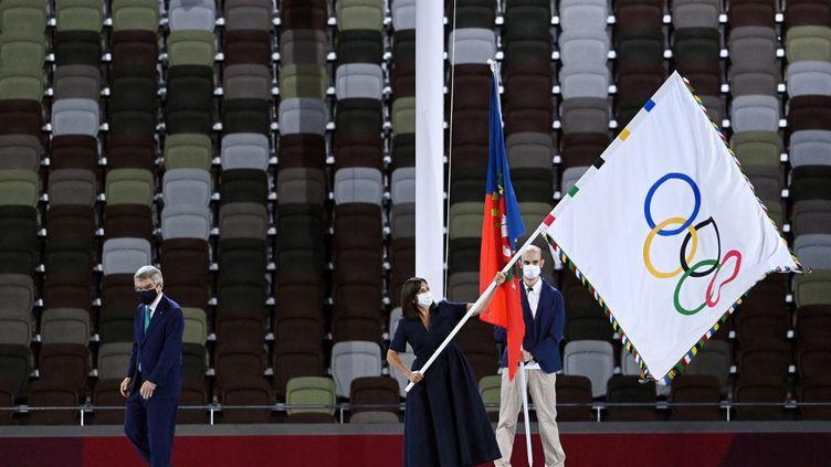 La maire de Paris, Anne Hidalgo, brandit le drapeau olympique lors de la cérémonie de clôture des Jeux olympiques de Tokyo, le 8 août 2021. (KEMPINAIRE STEPHANE / KMSP / AFP)