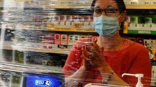 Une buraliste porte un masque derrière une protection en cellophane, le 25 mars 2020, à Reims (Marne). (FRANCOIS NASCIMBENI / AFP)