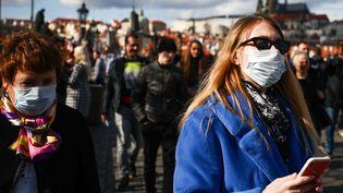 Des touristes portent des masques sur le pont Charles, à Prague, la capitale tchèque, le 1er mars 2020. (BEATA ZAWRZEL / NURPHOTO / AFP)