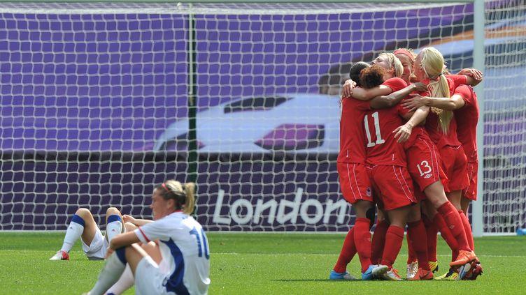 Les Françaises sont à terre et les Canadiennes à la fête après le but du Canada le 9 août 2012 aux JO à Coventry (Royaume-Uni). (PAUL ELLIS / AFP)