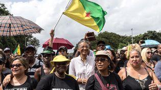 Le député Chantal Berthelot (en blanc, au centre), le 4 avril 2017 à Kourou (Guyane) lors d'une manifestation pour demander des hausses de salaire et de meilleures conditions de sécurité. (JODY AMIET / AFP)
