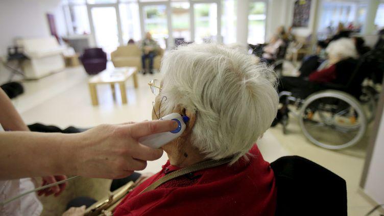 Une soignante prend la température d'une résidente d'un ehpad, durant la crise sanitaire. Photo d'illustration. (FRANTZ BOUTON / MAXPPP)