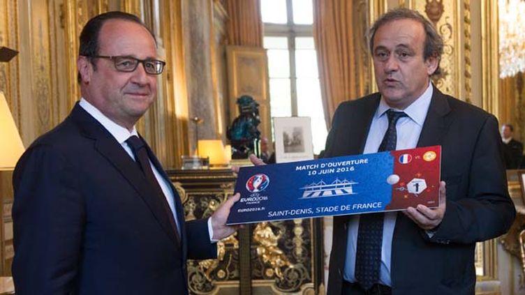 (En marge de la conférence de presse, Michel Platini a remis ce mercredi à François Hollande un billet symbolique pour le match d'ouverture de l'Euro 2016 en France © MaxPPP)