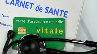 Cette photo pris le 14 mai 2016 à Paris montre une carte Vitale et un carnet de santé. (FRANCK FIFE / AFP)