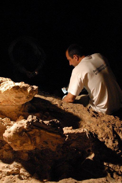 Le chercheur français Laurent Bruxelles au chevet de Little Foot dans la grotte de Sterkfontein =(Afrique du Sud) en 2010 (FRANCIS DURANTHON / TOULOUSE MUSEUM / AFP)