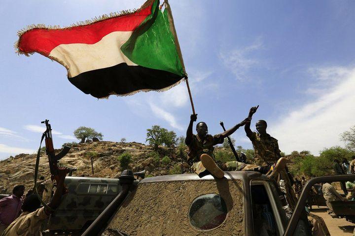 Les soldats de l'armée soudanaise brandissent le drapeau soudanais le 20 mai 2014 après avoir repris la zone de Daldako, à l'est de la capitale du Sud-Kordofan, Kadugli.   (REUTERS/Mohamed Nureldin Abdallah )