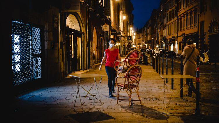 La gérante d'un bar se prépare à fermer son établissement à l'approche du couvre-feu, le 21 octobre 2020 à Toulouse (Haute-Garonne). (LILIAN CAZABET / HANS LUCAS / AFP)