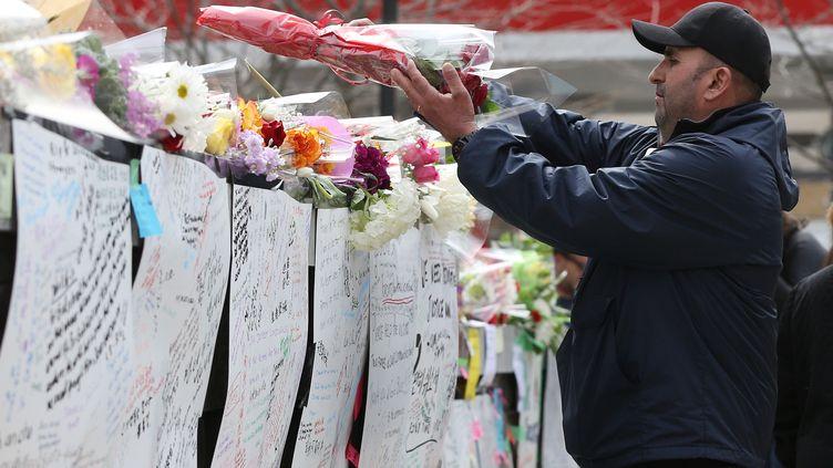 Un homme dépose des fleurs, le 24 avril 2018, sur un mémorial rendant hommage aux victimes de l'attaque à la voiture bélier de Toronto (Canada), qui a fait 10 morts la veille. (LARS HAGBERG / AFP)