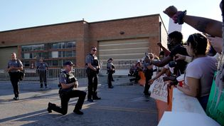 Un policier met un genou à terre en soutien aux manifestants contre les violences policières, à l'extérieur du commissariat d'Oklahoma City, aux Etats-Unis, le 31 mai 2020. (NICK OXFORD / REUTERS)