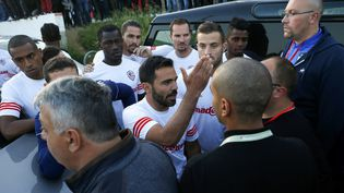 Le capitaine de l'équipe de l'AC Ajaccio essaie de parler avec les joueurs du Havre alors le bus de ces derniers était endommagé par des supporters corses. (PASCAL POCHARD-CASABIANCA / AFP)