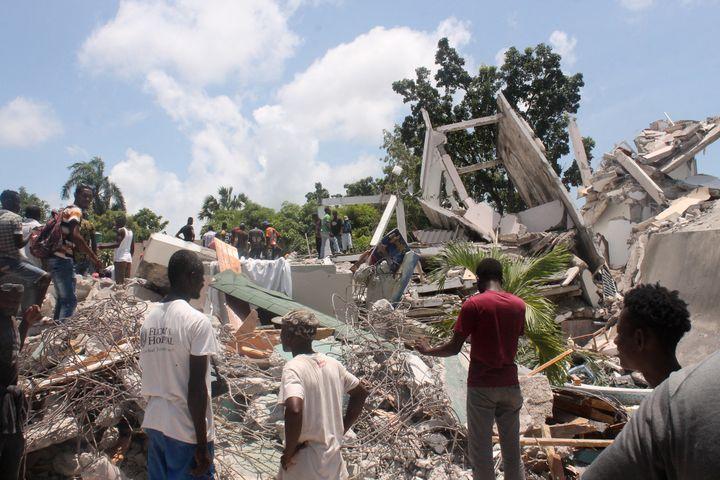 Des Haïtiens fouillent les décombres de l'hôtel Le Manguier auxCayes, après le tremblement de terre survenule 14août 2021. (STANLEY LOUIS / AFP)
